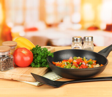 Vegetable ragout in pan,  on wooden table on bright background