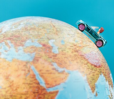 Toy car on the globe on plain blue background. Space for text