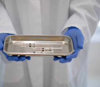 A person wearing a lab coat and blue protective gloves holds a metal tray in their hands, with three loaded syringes on it.