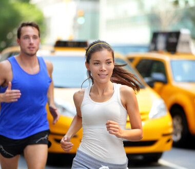Active couple running on famous shopping street fifth avenue in Manhattan, New York City NYC, USA. Exercise lifestyle portrait of young asian woman runner and caucasian male jogger.