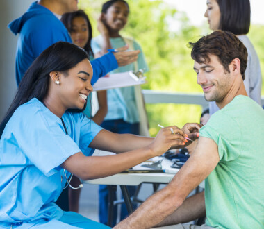 Mid adult Caucasian man smiles as African American nurse gives him a shot in his left arm. He is receiving a free medical exam and immunizations at a community outdoor free clinic. Patients and volunteers are standing in the background talking.