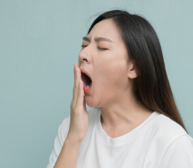 asian young Women yawn on light blue background.