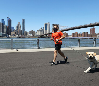BROOKLYN, NEW YORK  - APRIL 28:  A Man runs with his dog while wearing a mask amidst the coronavirus pandemic at Brooklyn Bridge Park on April 28, 2020 in the Brooklyn Borough of New York City.  The World Health Organization declared coronavirus (COVID-19) a global pandemic on March 11th.  (Photo by Al Bello/Getty Images)