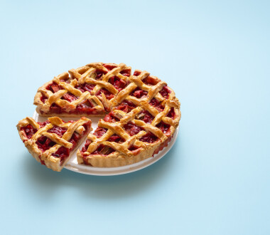 Rhubarb and strawberry pie sliced in portions, isolated on a  blue seamless background. German rhubarb cake. Handmade sweet pie on white plate.