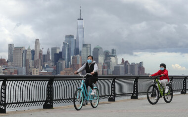 HOBOKEN, NJ - MAY 1: People wear masks as they ride their bicycles in front of the skyline of lower Manhattan and One World Trade Center in New York City on May 1, 2020 in Hoboken, New Jersey. (Photo by Gary Hershorn/Getty Images)