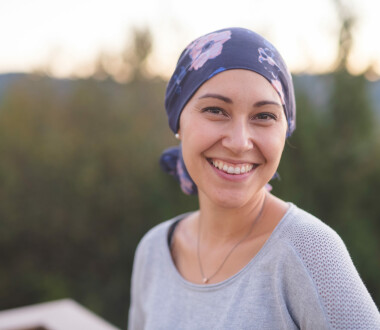 A beautiful young ethnic woman wearing a head wrap looks toward the camera and smiles radiantly. She is standing outdoors and there are mountains and trees in the background.