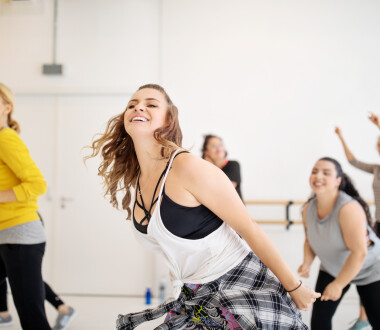 Cheerful  dance instructor teaching students in class. Multiracial women enjoying a dance routine at health club.