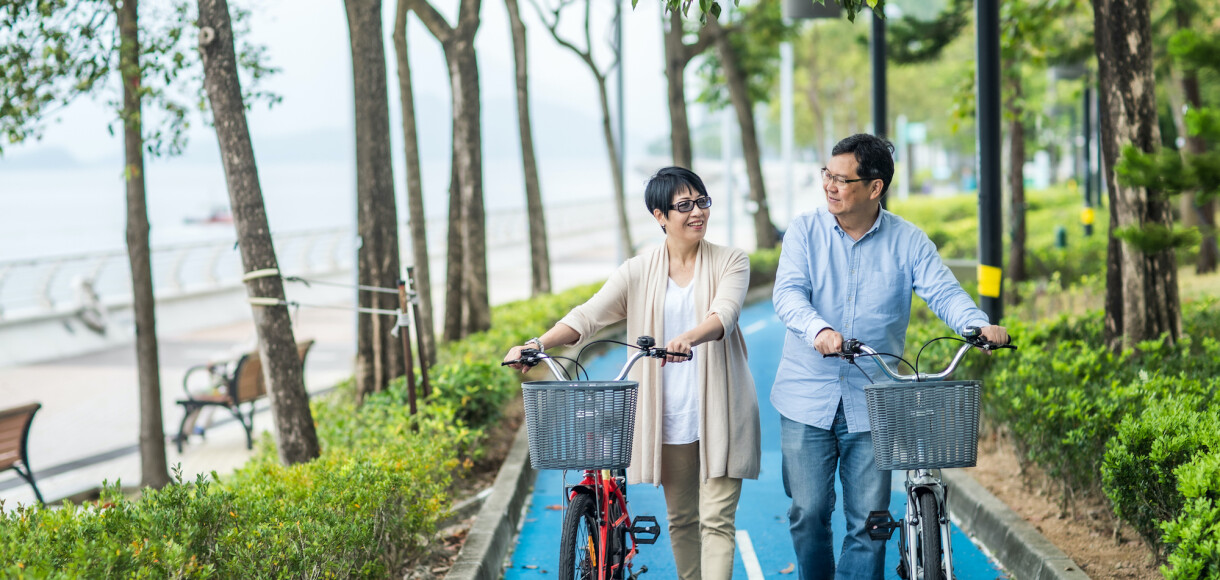 Senior couple with bicycles in the park.