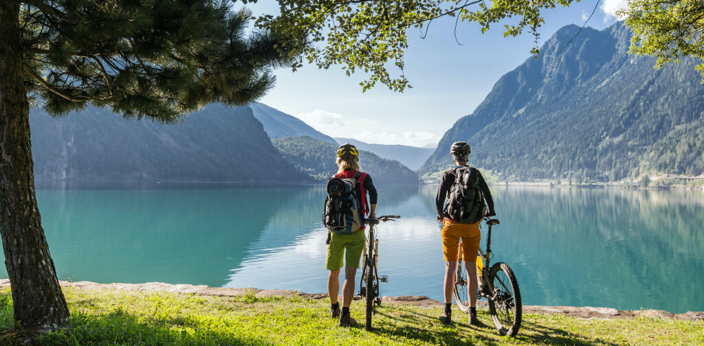 Two female Mountainbikers are taking a brake at lake Poschiavo, which is a natural lake in the Poschiavo valley.Poschiavo is a municipality in the district of Bernina in the canton of Graubünden in Switzerland.