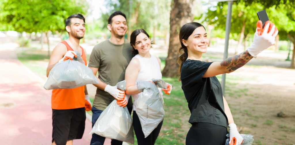 Beautiful young woman and her group of diverse friends taking a selfie with her smartphone after running while picking up trash outdoors