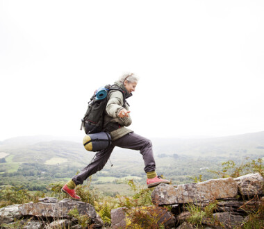 Older woman happily trekking in the mountains of ireland, solo travelor enjoying freedom and independence.